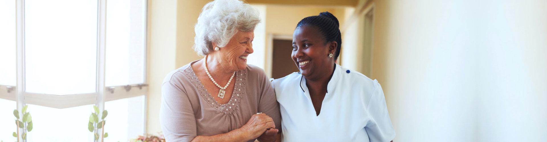 caregiver assisting senior woman walking and smiling